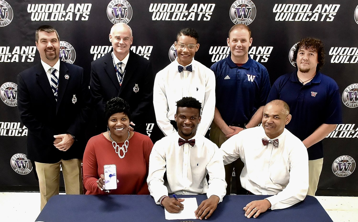 Recent Woodland High graduate Titus Jones signed to play football at Alabama A&M in Huntsville. On hand for the signing were, from left, front row: Marilyn Jones, mother; Stephen Jones, father; back row, John Howard, WHS athletic director; Wes Dickey, then-WHS principal; Caleb Jones, brother; Tony Plott, WHS head football coach; and Mark Middleton, WHS assistant football coach. Marilyn Jones also held a cell phone to allow Titus Jones' brother, Emmanuel, to video chat during the ceremony.