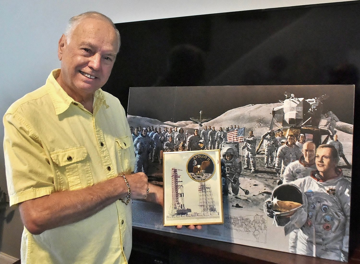 David Denault, in front of a picture combining the images of all of the astronauts to walk on the moon, holds a picture of Apollo 11 on the launch pad and the official Eagle patch representing the moon landing.