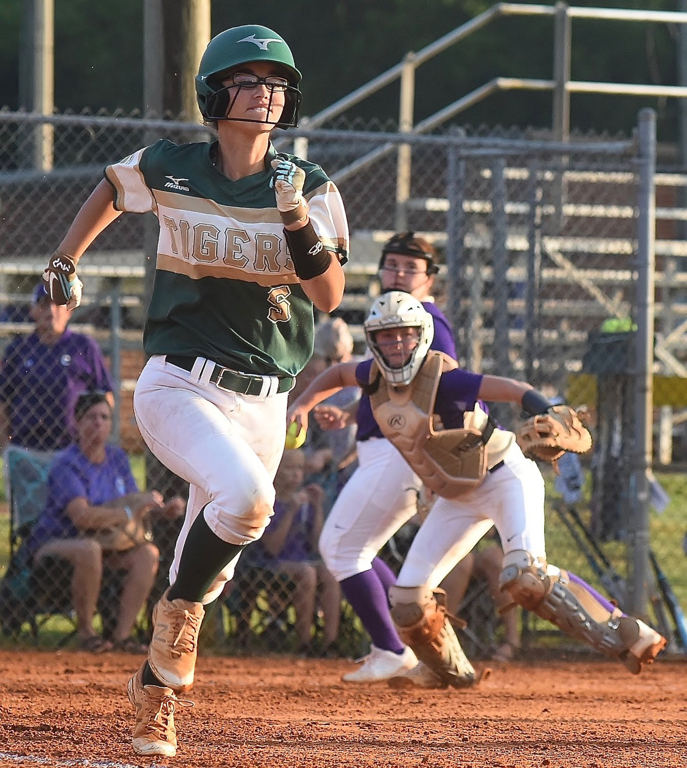 Adairsville outfielder Makayla Wade runs up the first-base line after a bunt, while Cartersville catcher Lauren McElhaney prepares to successfully throw her out.