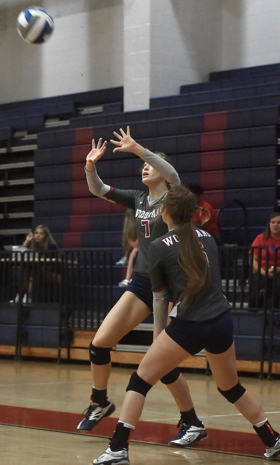 Woodland senior Grace Webb (7) sets the ball as teammate Emmalee Cigainero looks on during Tuesday's home match against Chattooga.