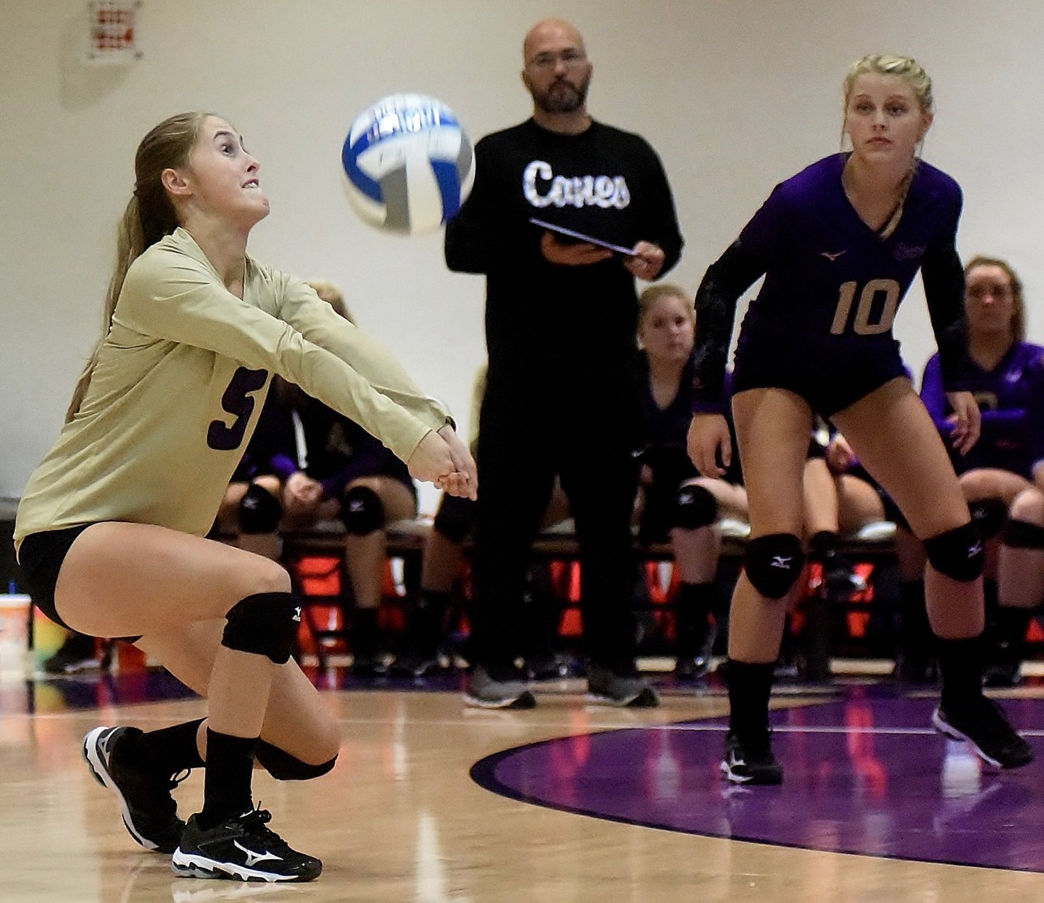 Cartersville libero Layne Condra (5) digs the ball, as Canes coach Dutch Cothran and teammate Anna Grace Brock watch, during a home match against Rome on Monday at The Storm Center.