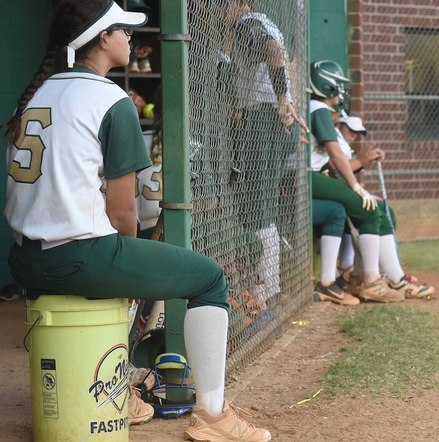 Adairsville's Makayla Wade, left, and several of her teammates wait and watch Tuesday afternoon as the umpires and coaches for the host Tigers and visiting Calhoun determine the proximity of lightning to the field, which caused the game to be stopped in the first inning. The contest was ultimately postponed until 5:30 Wednesday.