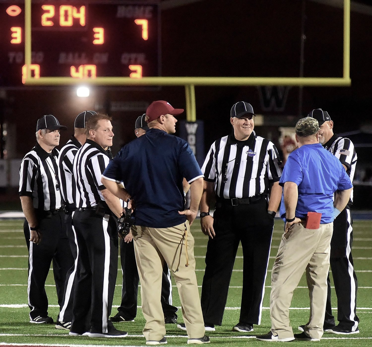 Woodland head coach Tony Plott, left, and Cass head coach Bobby Hughes discuss the lightning delay with game officials Friday night at Wildcat Stadium. Cass was leading Woodland by a score of 24-7 when the game was suspended a second time. The remainder of the game will resume at 7 p.m. today.