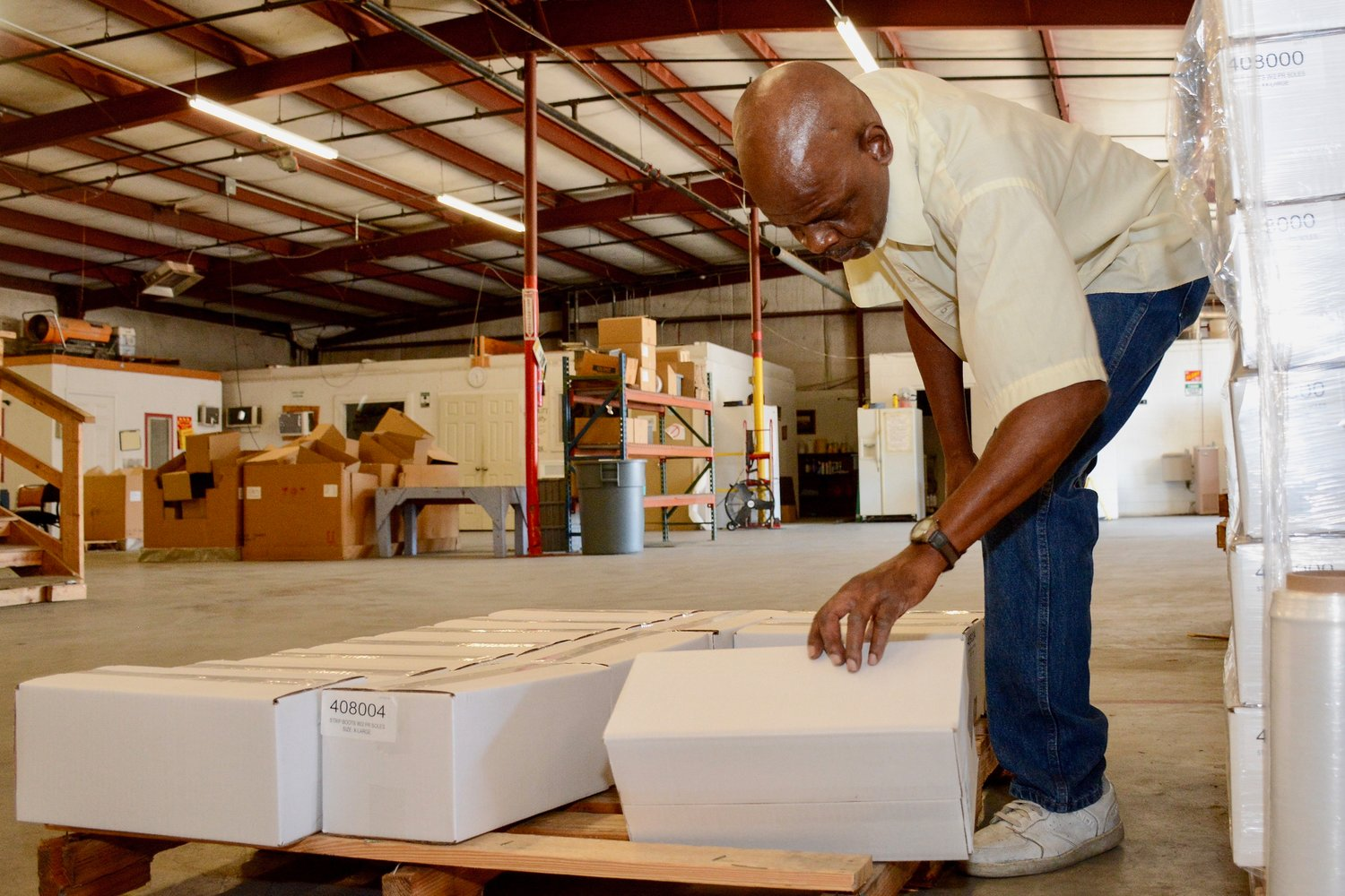 Good Shepherd Foundation Warehouse Assistant Robert Billingsley packs and palletizes Stripping Boots for Americo Manufacturing