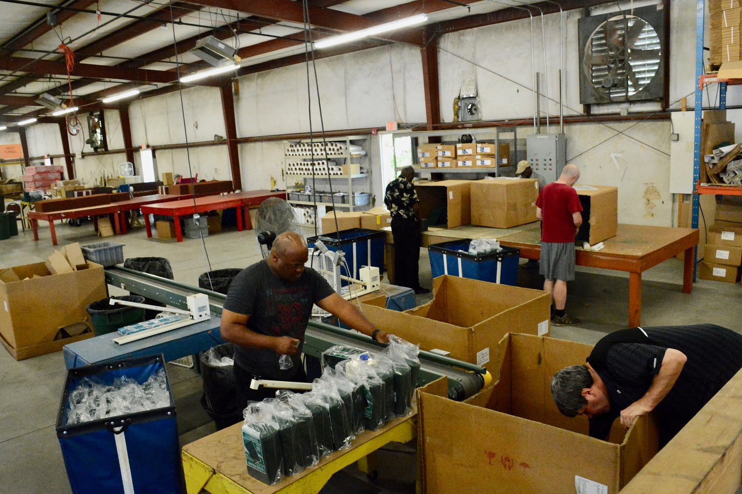 Lateef Onigbinde seals bags of sponges that are being packed and palletized by Ben Watkins for Americo Manufacturing.