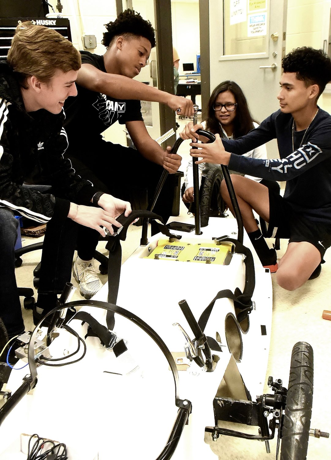 Bartow County College & Career Academy mechatronics students, from left, Logan Queen, Ja'Maury Johnson, Britany Gomez, and Omar Garcia work on the electric car they built to participate in Tellus Science Museum's Heavy Metal in Motion event Saturday from 10 a.m. to 4 p.m.