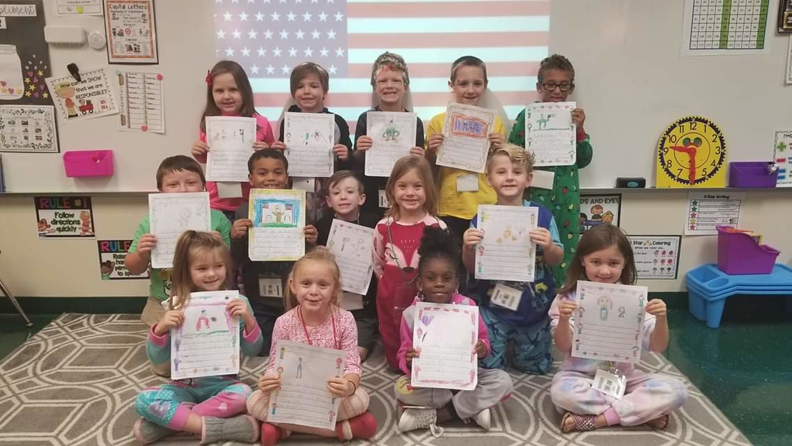Students in Jenna Ray's first-grade class at White Elementary School show off the holiday letters they wrote to servicemen and women as part of Bert's Big Thank You letter-writing campaign.