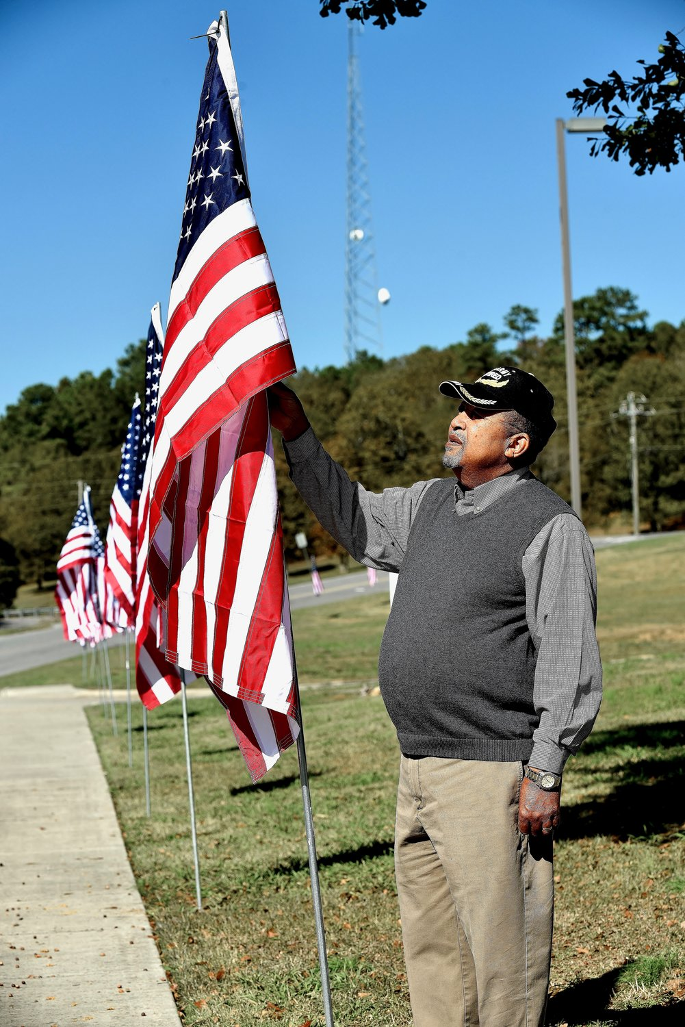 Retired U.S. Army veteran David Ford of Euharlee makes adjustments to one of the flags on display along Covered Bridge Road, commemorating Veterans Day.