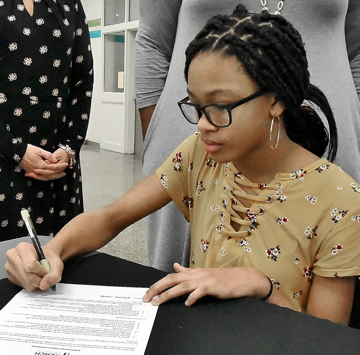 Red Top Middle School eighth grader Tyreana Sims signs her REACH Scholarship contract Thursday at the REACH Scholarship signing ceremony at the Bartow County College & Career Academy.