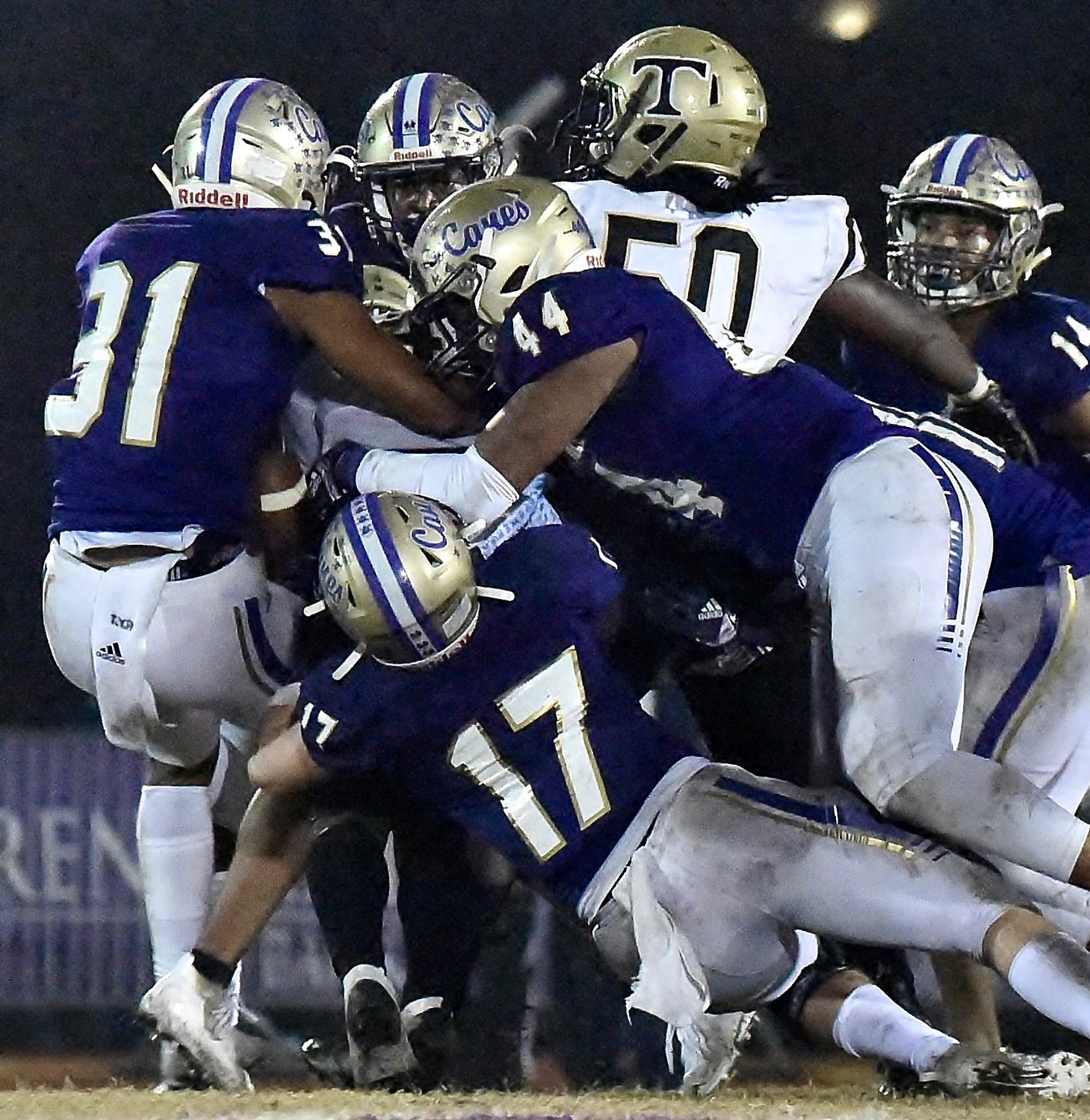 A group of Cartersville defenders led by, from left, Amarai Orr (31), Gavin Geros (17) and Emmanuel Hayes (44) take down a Thomson ballcarrier during a Class 4A state second-round matchup Friday at Weinman Stadium. The Canes will host Woodward Academy this week in the quarterfinals.