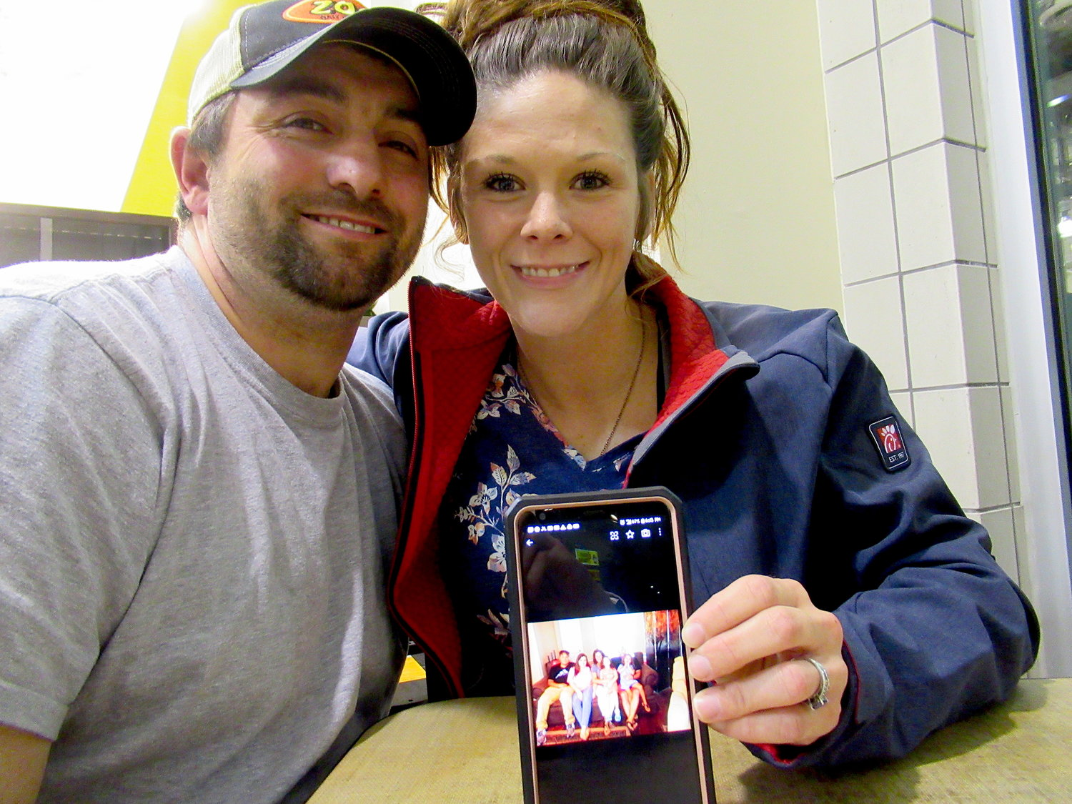 Nicholas McFall, 36, and Stephanie McFall, 30, show off a photograph of themselves with their children.