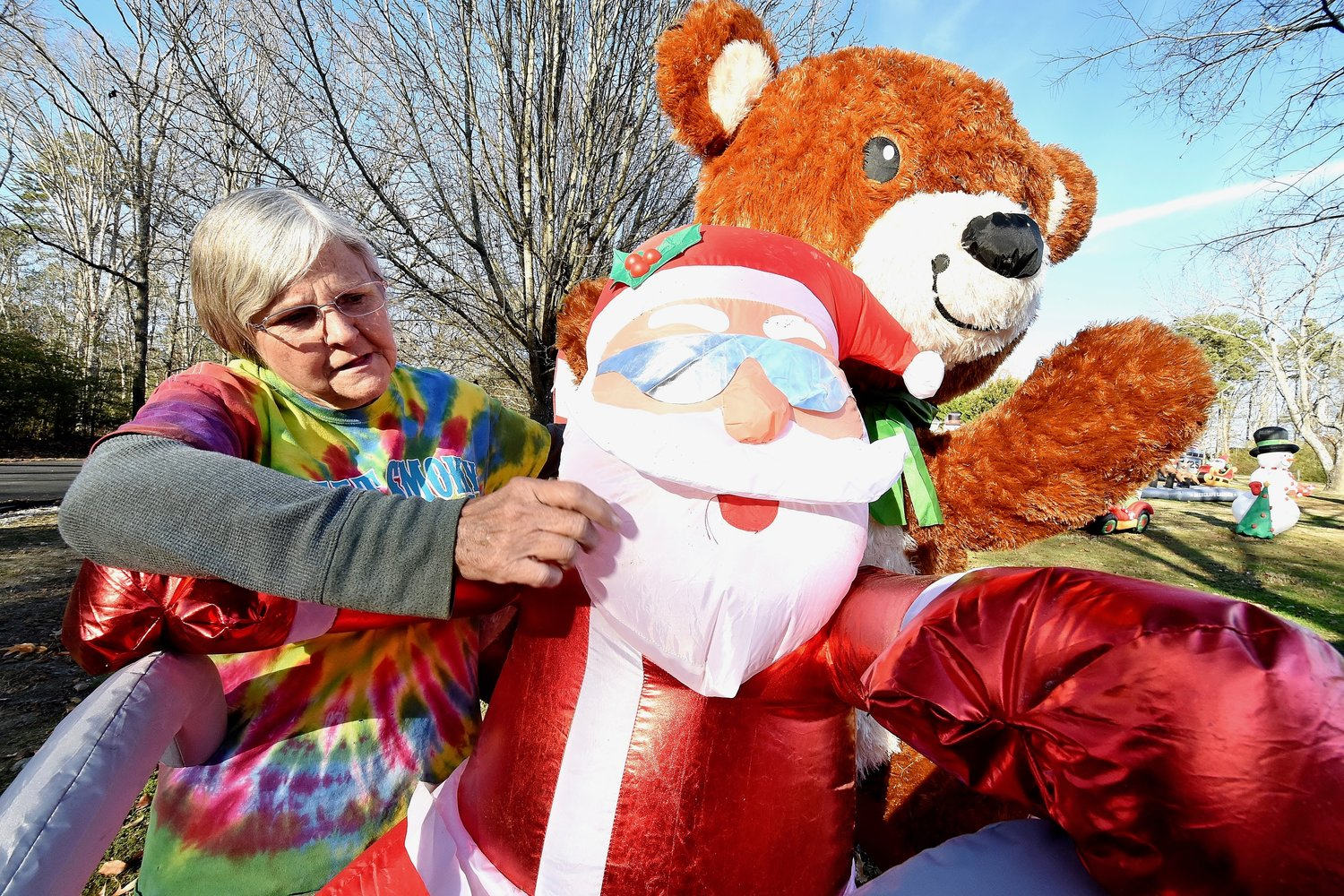 Sheila McGuirt makes adjustments to a Santa and teddy bear inflatable that she refers to as one of her favorites among the more than 300 inflatables on their property.
