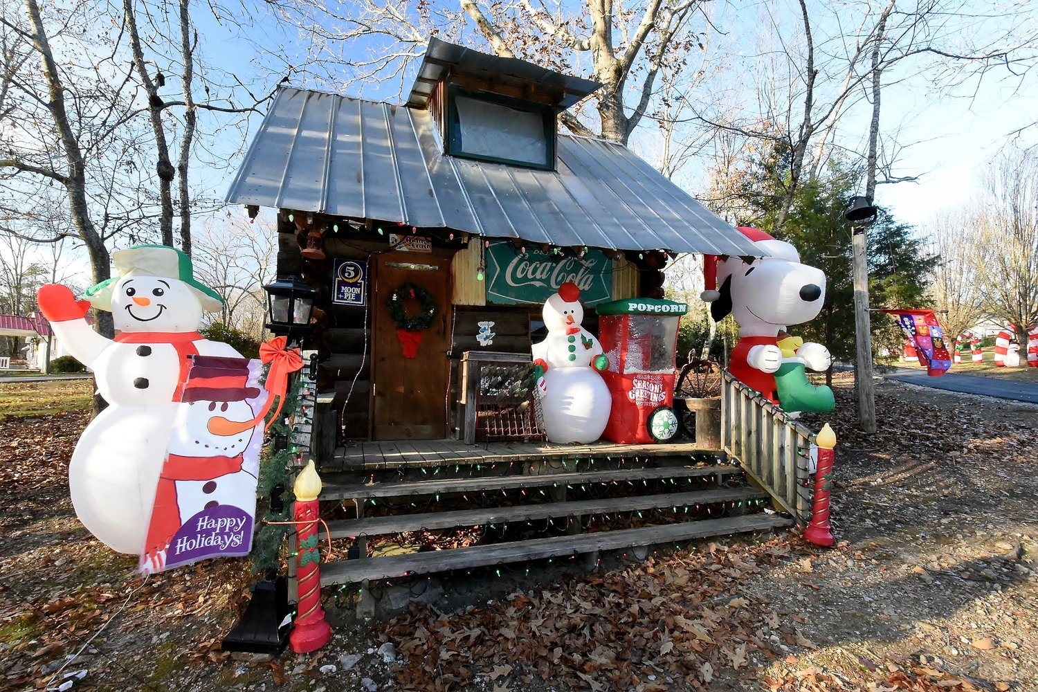 A general store with a window featuring a Christmas video is surrounded by inflatables and lights of different colors and sizes.