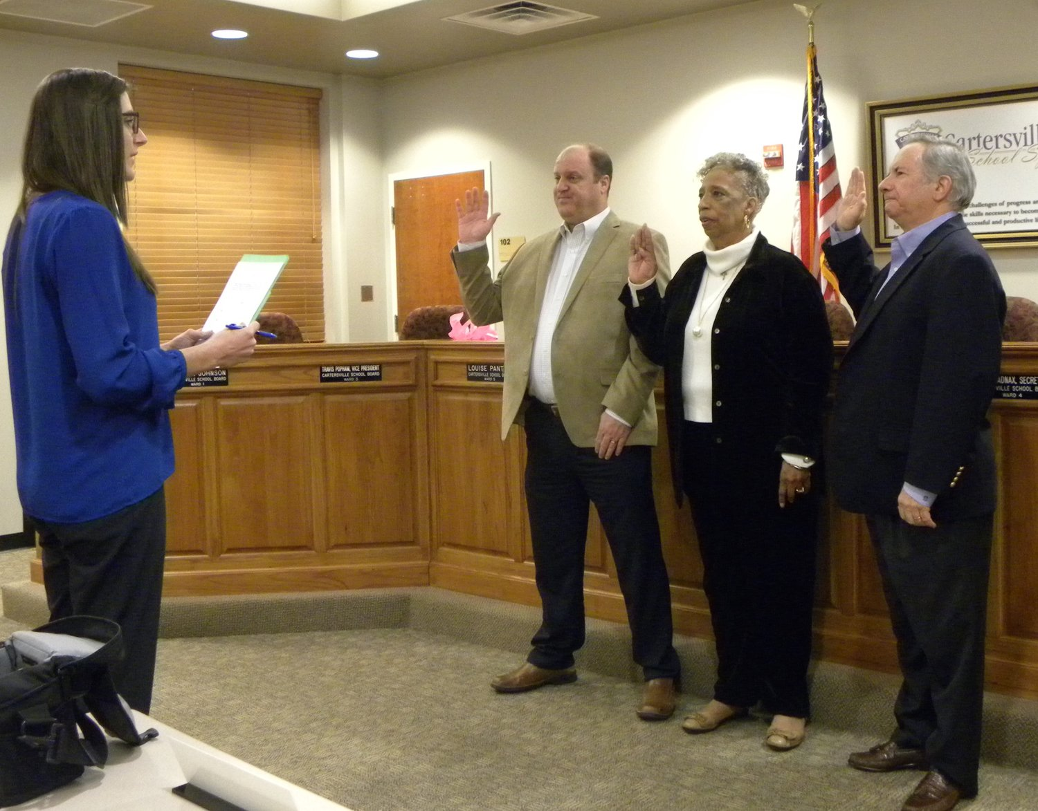 Cartersville City School Board members, from left, Travis Popham, Pat Broadnax and Tim Chason begin their new terms by taking the oath of office administered by Cartersville City Clerk Meredith Ulmer at Thursday night's work session.