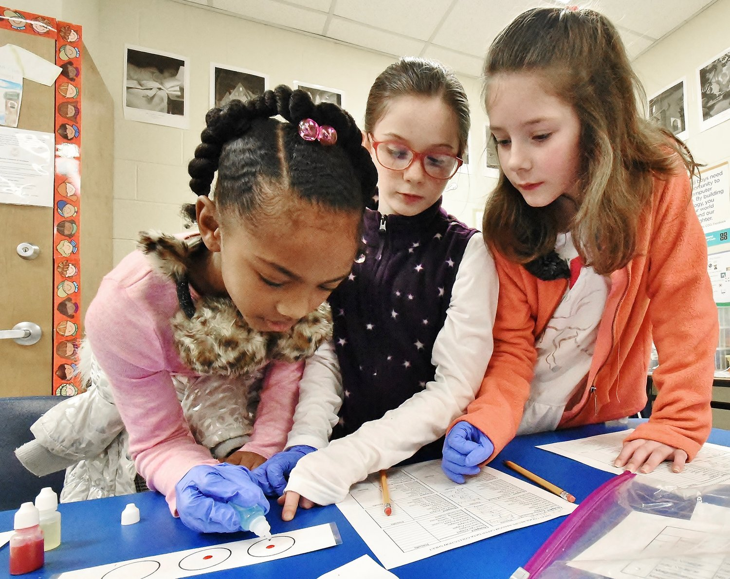 Kingston Elementary School third graders, from left, Kamillah Richardson, Katelyn Carroll and Madison Eubanks test evidence in an attempt to solve a forensics case.