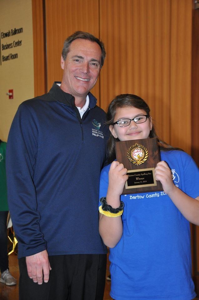 Bartow County Superintendent Dr. Phillip Page presented the winner's plaque to spelling bee champion Leilah Bedford.