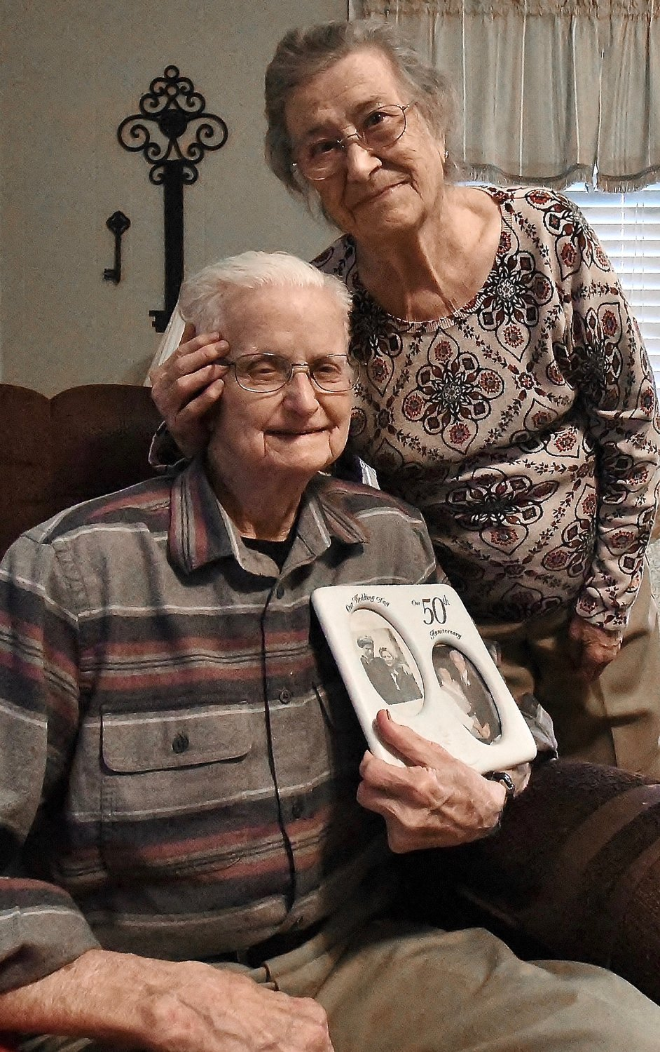 Omie Whitener embraces Jack, her husband of 74 years, as he holds a frame displaying a photograph of the couple in March 1945 and another image at their 50th wedding anniversary celebration.