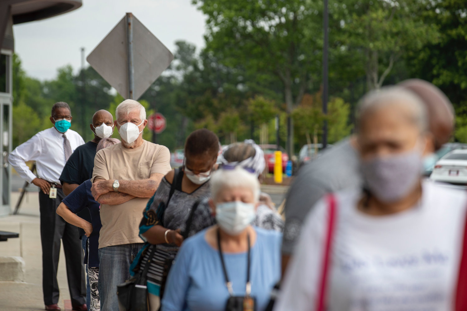 Voters wearing face masks stand in line outside of the Gwinnett County Voter Registration and Elections Office in order to participate in early voting in Lawrenceville on Monday.