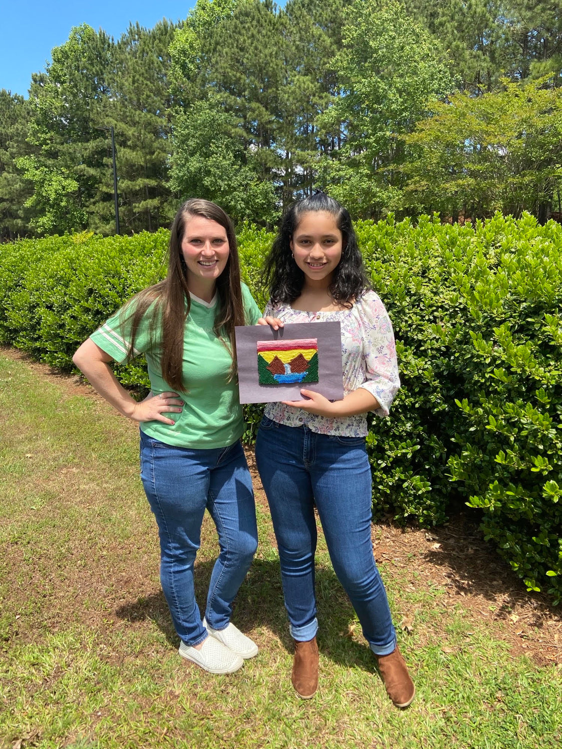 "Allatoona Elementary fifth-grader Sophia Vasquez-Munguia, with her art teacher, Kaycie Nix, shows off her ""Mountain Falls"" yarn painting that won her the 2020 Purchase Award for The Primary and Elementary School Virtual Art Exhibit on the Booth Western Art Museum's website."