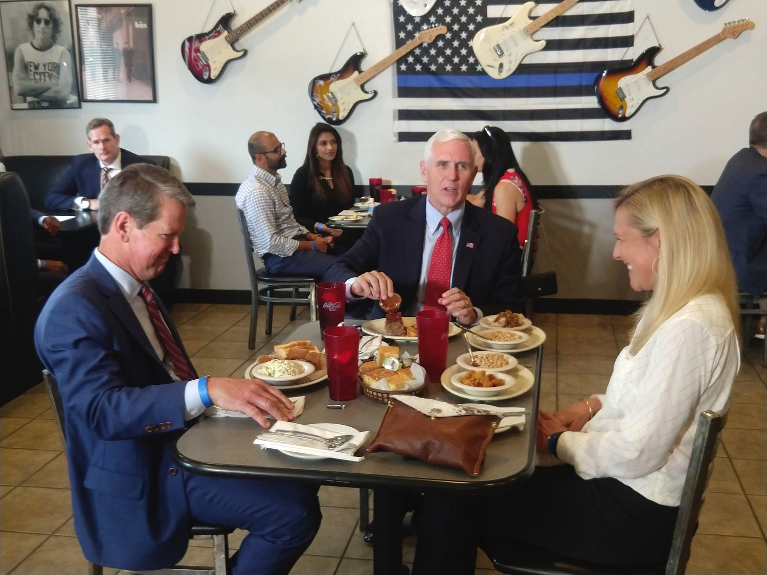 "Vice President Mike Pence eats lunch with Georgia Gov. Brian Kemp and his wife Marty Kemp at the Star Cafe in Atlanta Friday. Pence said Georgia was ""leading the way"" and the country was making progress against the coronavirus."