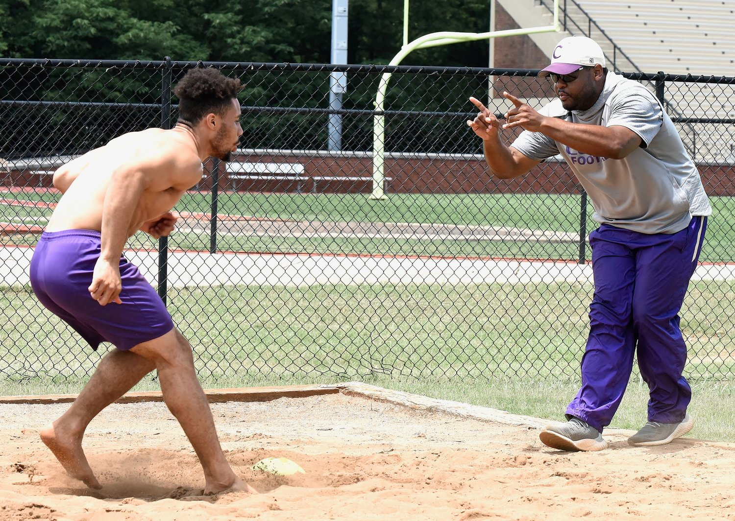 Cartersville rising senior Rashar Locklear is directed by wide receivers coach Jim Jones Tuesday during a drill in a sandpit set up near the Canes practice field.