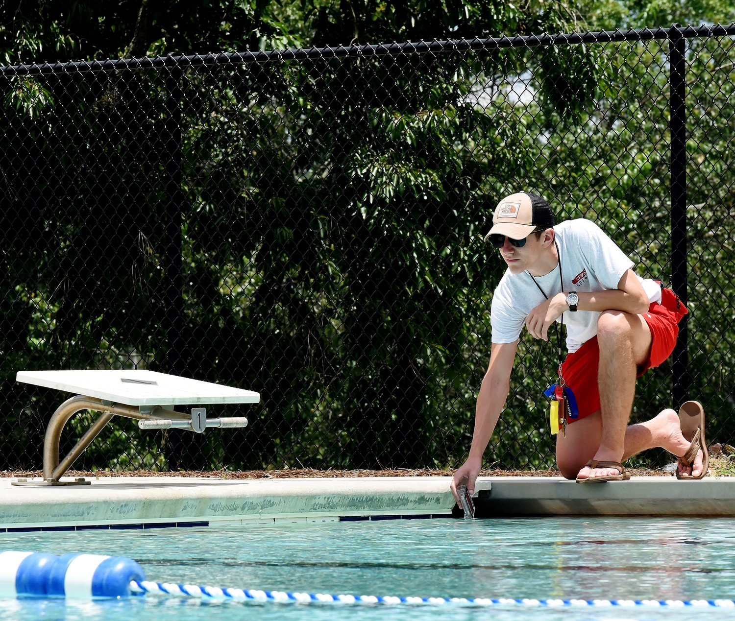 Lifeguard Thomas Peters checks the water quality at the Dellinger Park pool. The pool is scheduled to open June 11.