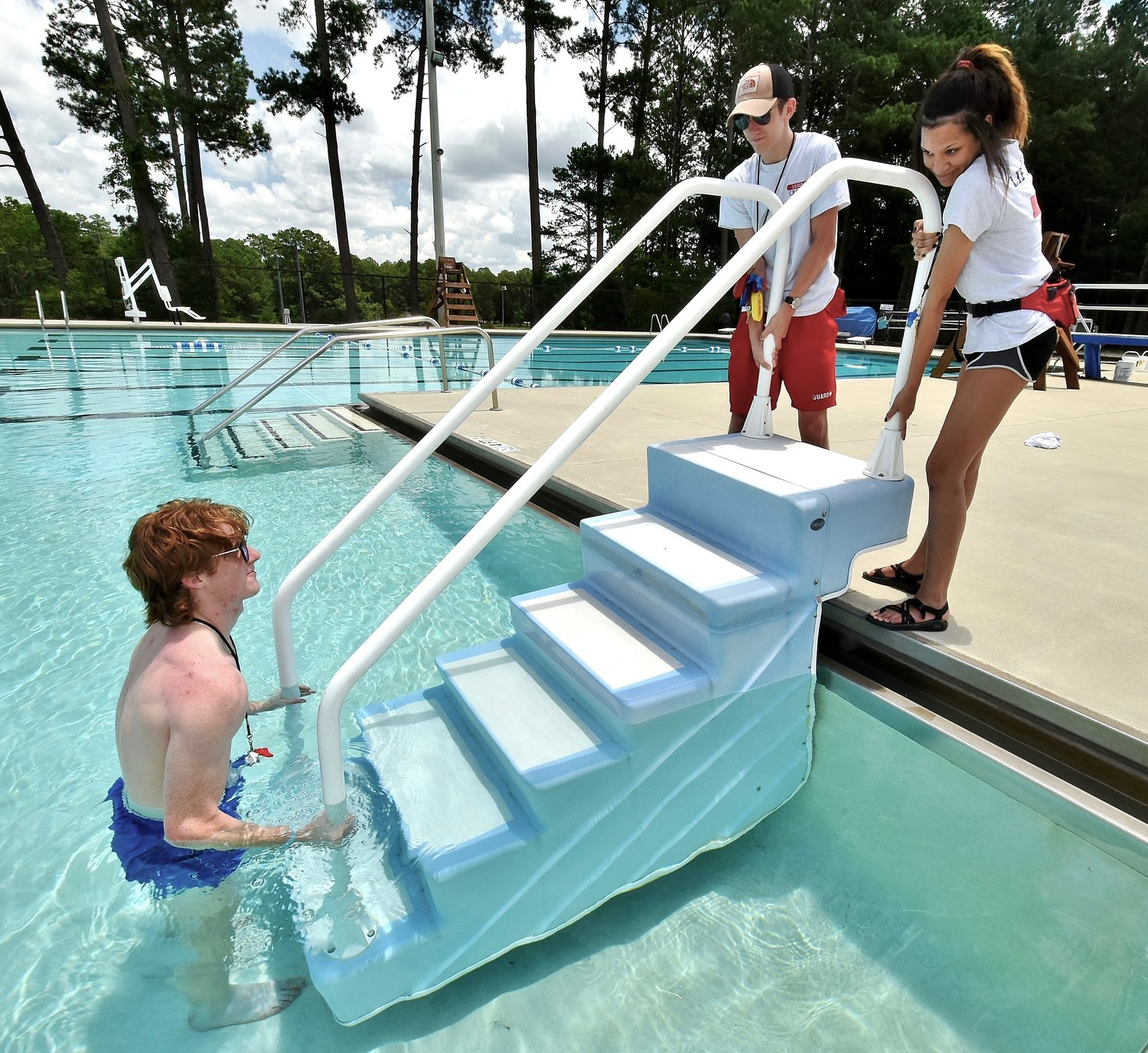 Lifeguards, from left, Cason Vogelsang, Thomas Peters, and Kaya Smith position the moveable steps in the Dellinger Park pool. The pool is scheduled to open June 11.