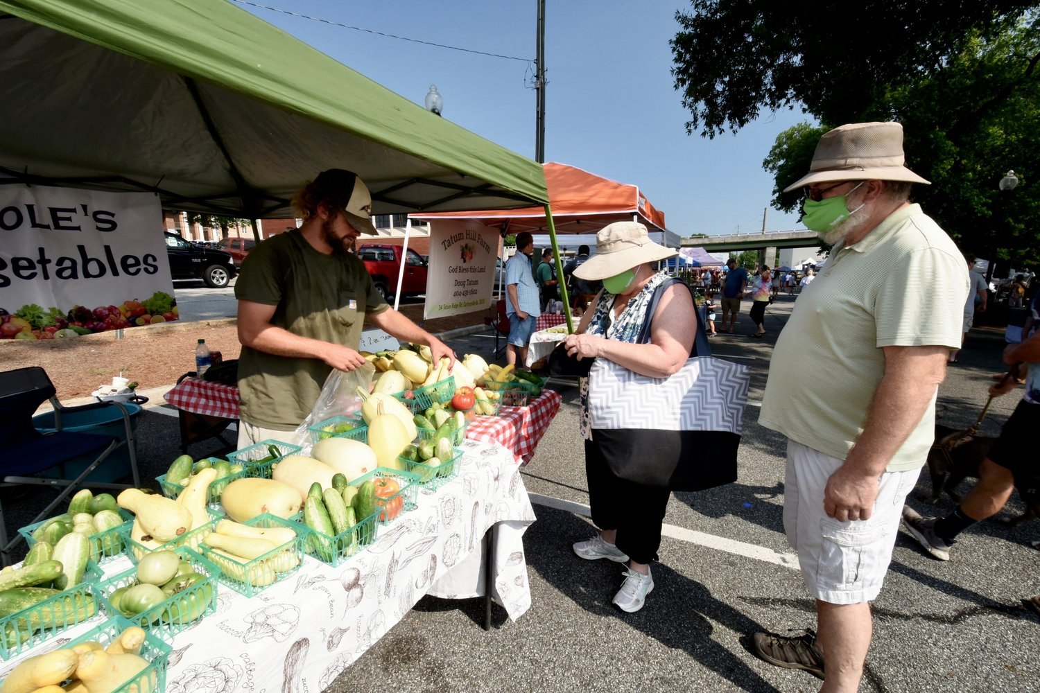 Many shoppers at the Cartersville Farmers Market, including this couple purchasing goods from Evan Cole at his Cole's Vegetables tent, are taking precautions against COVID-19 by wearing a mask.
