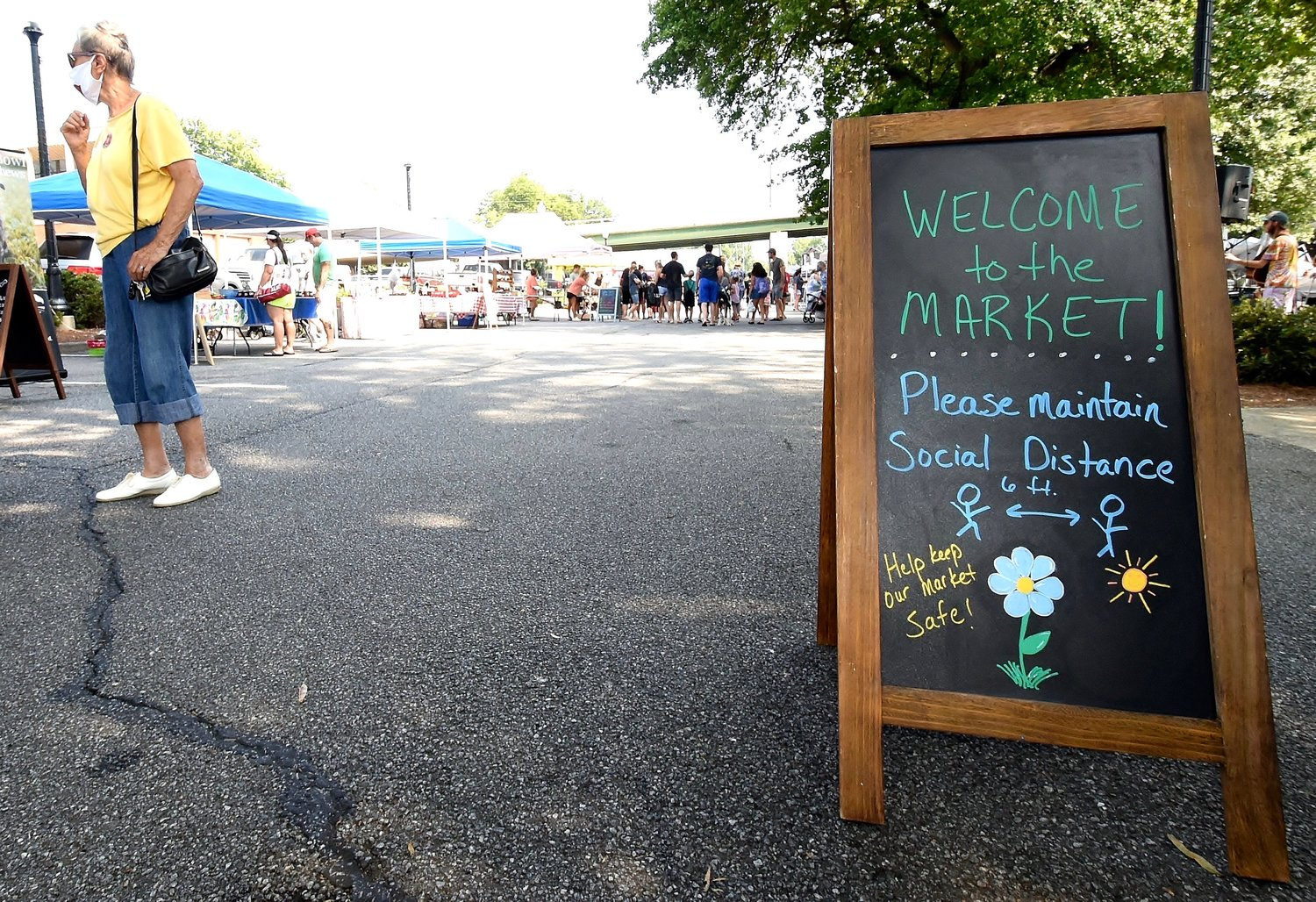 A sign near the Cherokee Avenue entrance to the Cartersville Farmers Market encourages shoppers to practice social distancing.