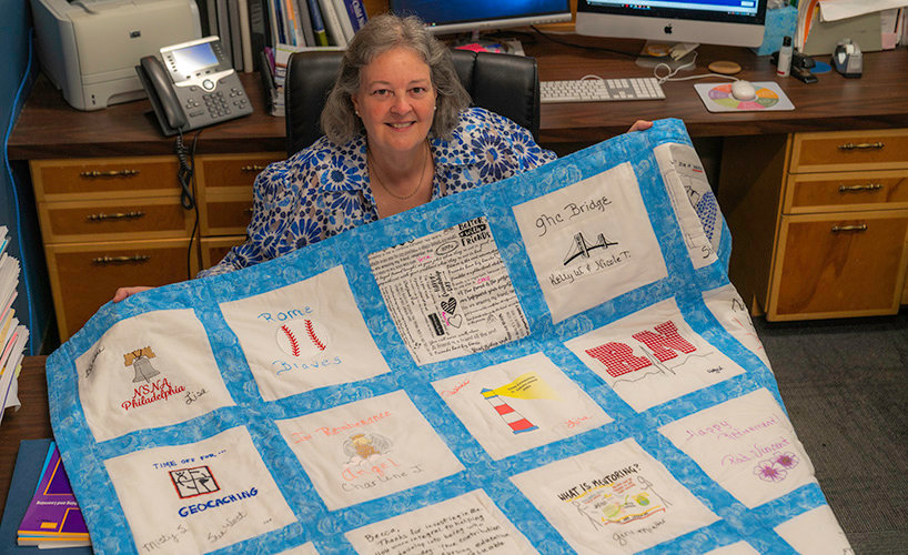 Georgia Highlands College Director of Nursing Becca Maddox shows off a quilt her co-workers made her for her retirement last month.