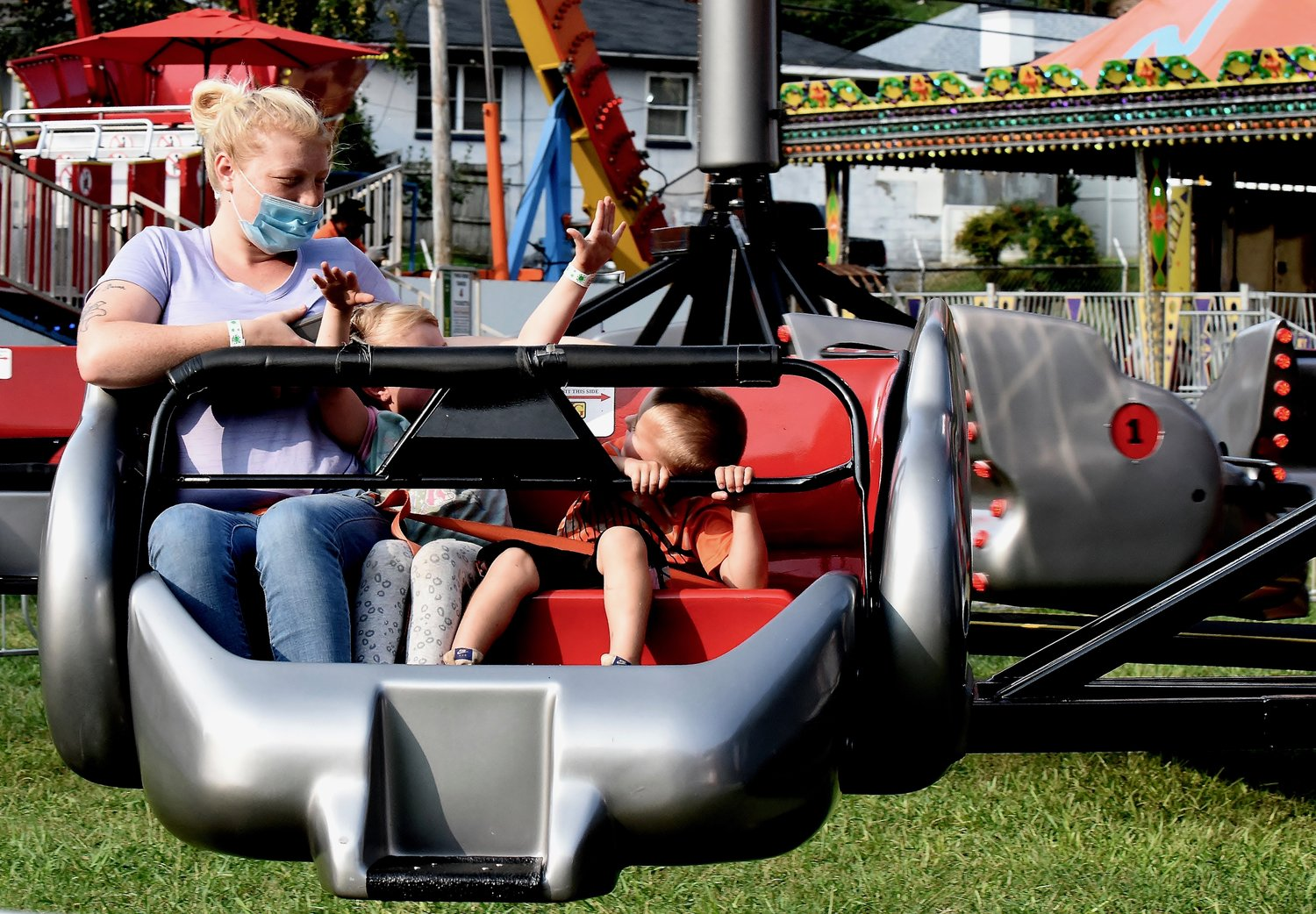 Along with 5-year-old Mallory Culver, center, and 3-year-old Jayden Culver, Haley Dover of Adairsville enjoys Peachtree Rides' carnival at American Legion Carl Boyd Post 42's Fairgrounds Wednesday.