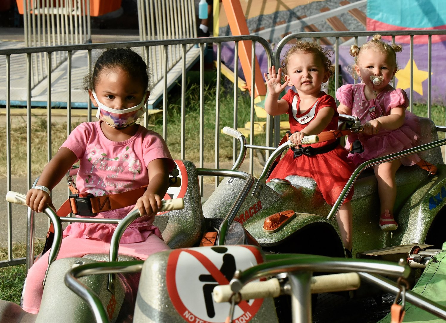 From left, 3-year-old Lilly Carter of Rome, Gloryann Jones-Bey, also 3, and her sister Cayleigh, 2, of Acworth, enjoy Peachtree Rides' carnival at the American Legion Carl Boyd Post 42 Fairgrounds Wednesday.