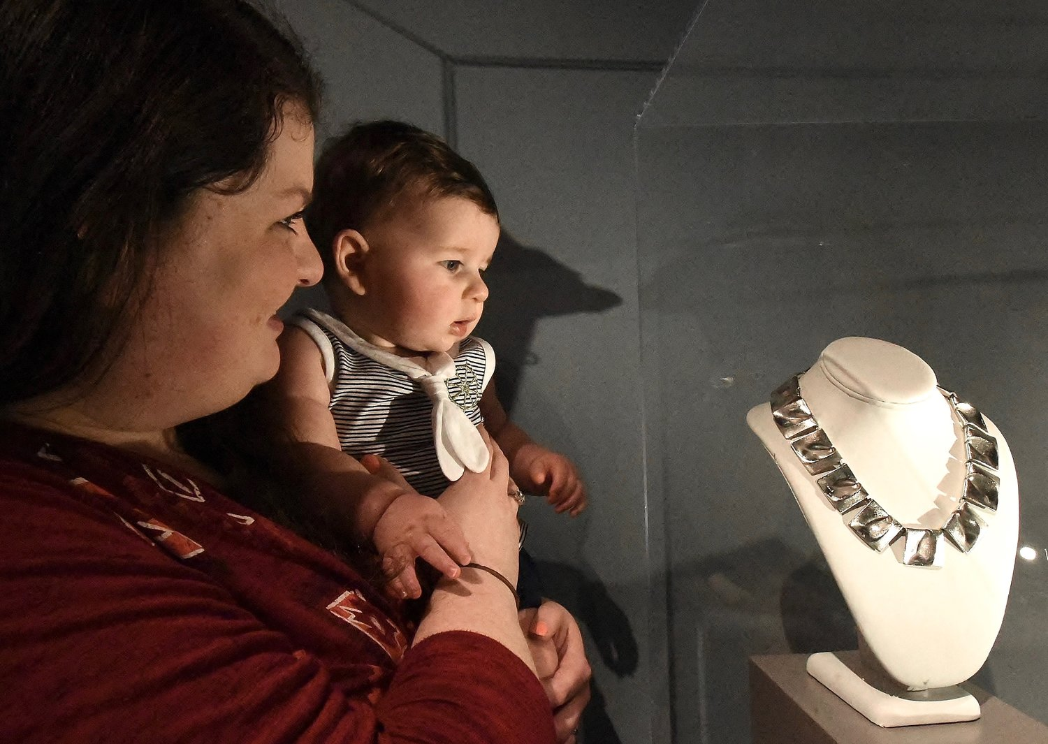 "Karmin Miller of Acworth and her 8-month-old son, Brantley, look at Princess Leia's necklace, one of the pieces chosen for Carrie Fisher to wear in the final scene of ""Star Wars: Episode IV — A New Hope."" The necklace is part of the ""Out of this World! Jewelry in the Space Age"" exhibit, which runs through Oct. 24, 2021, at Tellus Science Museum."