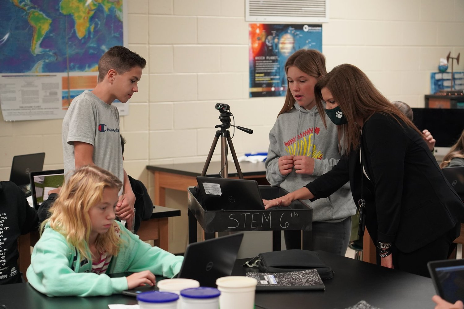 Adairsville Middle sixth-graders, from left, Sarenidy Powell, Ashton Evans and Ashlynn Durden and instructional lead teacher Brittany McCord make their presentation to state leaders during the final STEM walk for the school's state STEM certification last month.