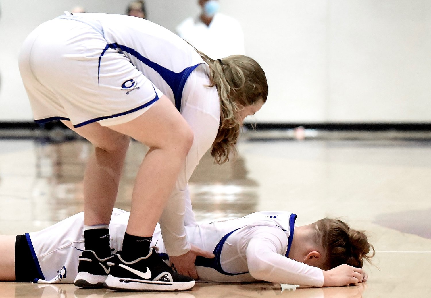 Cass junior Haley Johnson, standing, helps teammate Claire Davis off the floor after the Colonels fell to Hiram in the Region 7-AAAAA championship game Friday at The Storm Center. Davis scored a game-high 19 points in a 55-50 loss, which marked the first defeat of the season for previously unbeaten Cass.