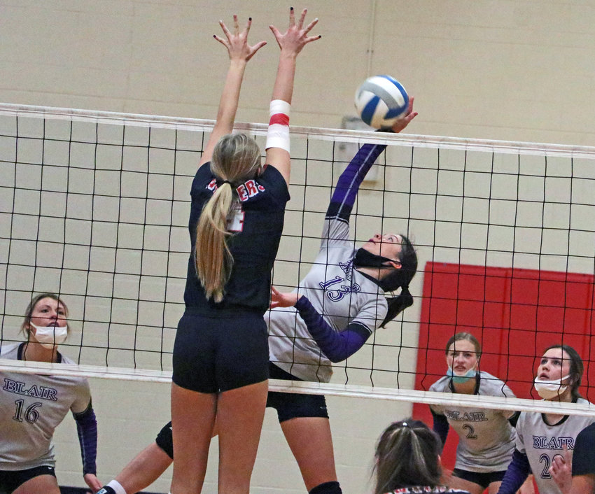 Blair sophomore Schuyler Roewert, middle right, hits the ball as the Antlers' Sydney Raszler tries to block it Saturday at Elkhorn High School.