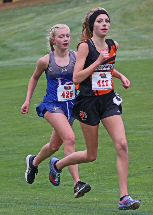 Fort Calhoun's Tessa Skelton, right, runs to the finish line Friday at Kearney Country Club.