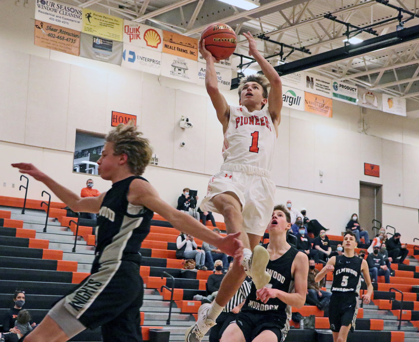 Pioneers senior Harrison Schmitt, middle, scores a layup Monday at Fort Calhoun High School.