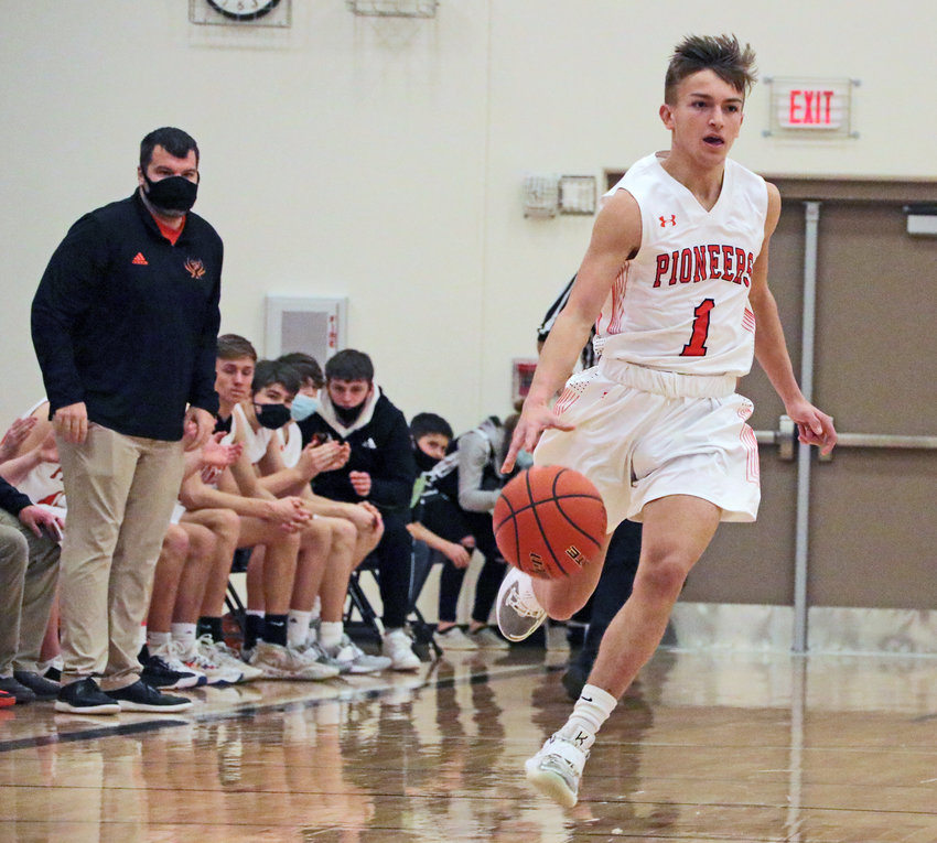 Pioneers senior Harrison Schmitt, right, dribbles the ball down the floor as coach TJ O'Conner watches Saturday at Fort Calhoun High School.