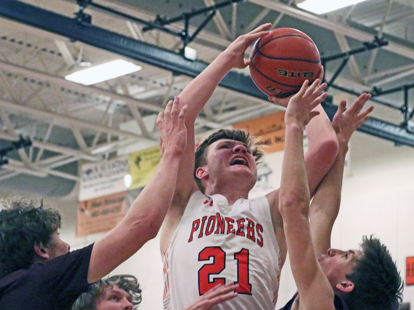 Pioneers junior Zane Schwarz is fouled by Arlington defenders Tuesday at Fort Calhoun High School.