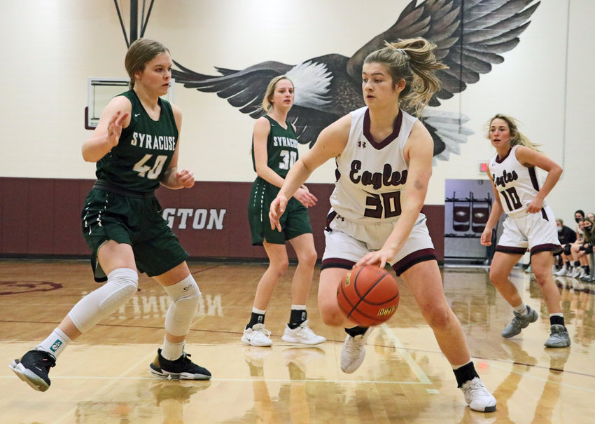 Eagles junior Kate Miller drives toward the basket as Syracuse's Klayre Roberts, left, defends Monday at Arlington High School.