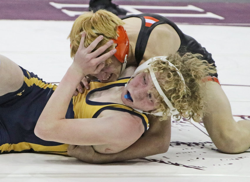 Fort Calhoun 113-pounder Ely Olberding, top, works to score back points against Raymond Central's Jacob Schultz on Friday in Omaha.