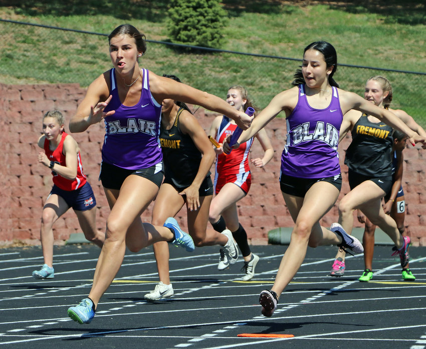 Blair Bears Grace Galbraith, left, and Erika Roehrs execute their 400-meter relay handoff Saturday at Ralston High School.