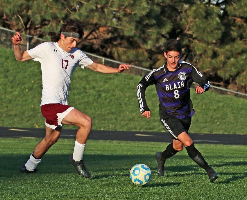 Blair midfielder Victor Dufau, right, dribbles downfield while defended by Waverly's Hap Christiansen on Tuesday at Krantz Field.