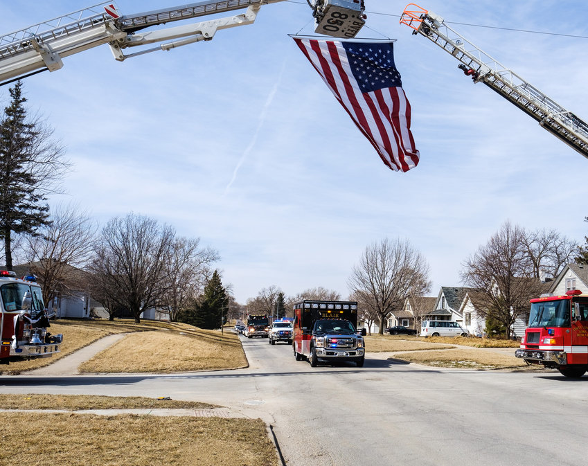 The American flag suspended from an aerial fire truck waves above 17th and Nebraska streets as the Clair McKinnis funeral procession passes Saturday.