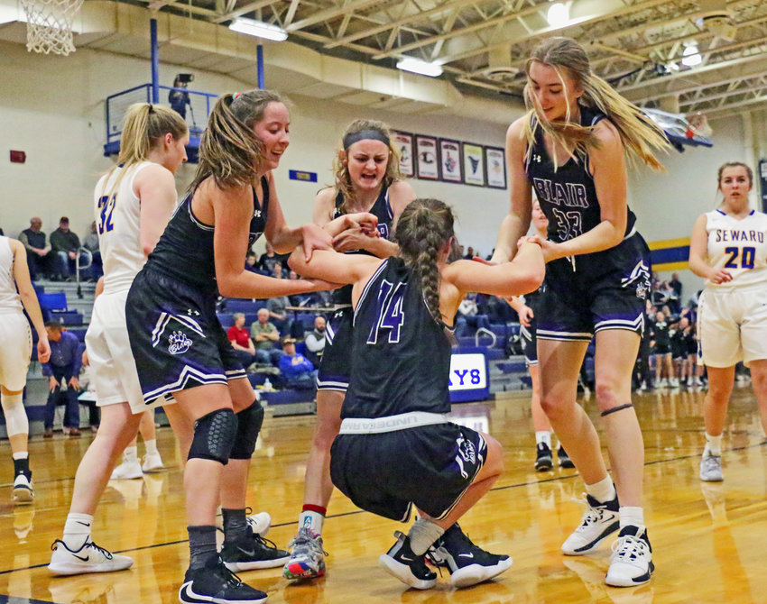 Blair's Makayla Baughman, from left, Mya Larson and Maicy Lourens help Sophia Grantham to her feet after a Bluejay foul Friday at Seward High School.