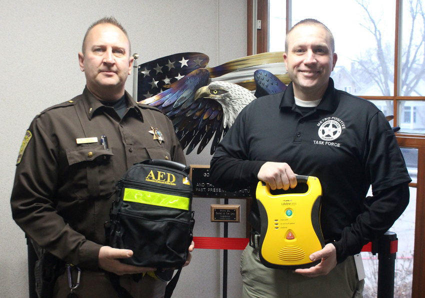 Lt. Butch Groves, left, and Capt. Aaron Brensel hold one of the 16 new automated external defibrillators that will be placed into patrol vehicles. The Washington County Sheriff's Office purchased the devices through donations.