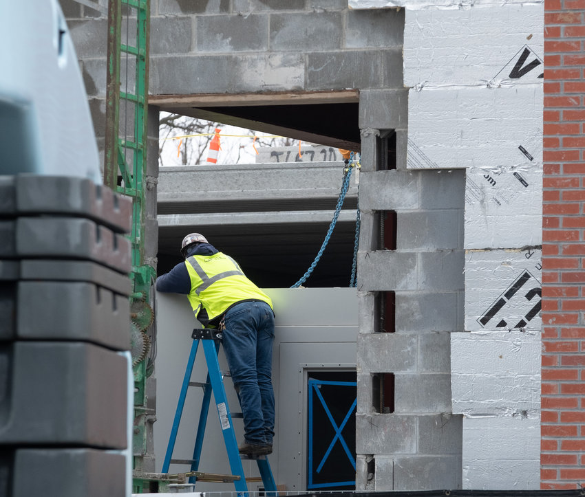 A construction crew member helps unhook a jail cell pod after it was placed by crane into the new Washington County Law Enforcement and Criminal Justice Center.
