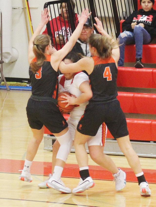 Sydney Guzinski (#3) and Mya Guzinski (#4) traps the Omaha Nation player with the ball.