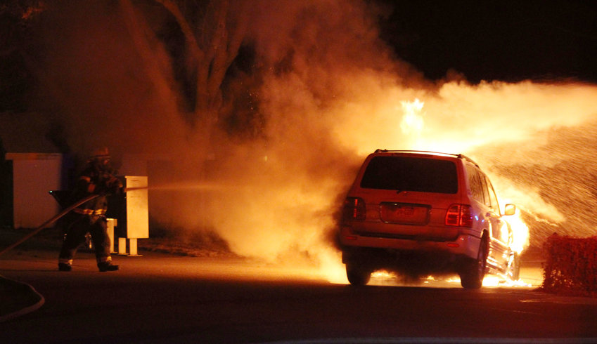 A Blair firefighter sprays water on a vehicle that caught fire while the owner was driving it Thursday night on his way home in Country Estates Mobile Home Park just south of Blair.